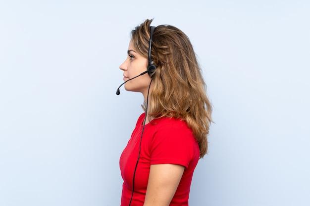 Jovem mulher loira trabalhando com fone de ouvido