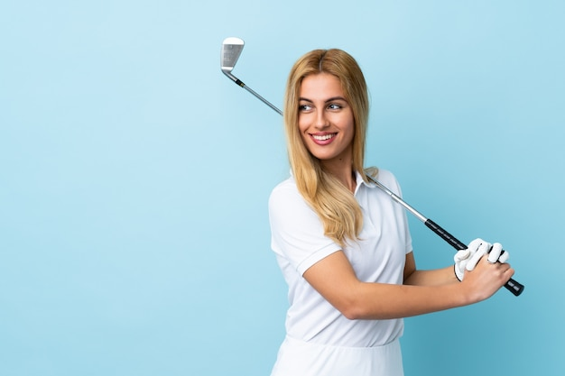 Jovem mulher loira uruguaia sobre parede azul isolada jogando golfe