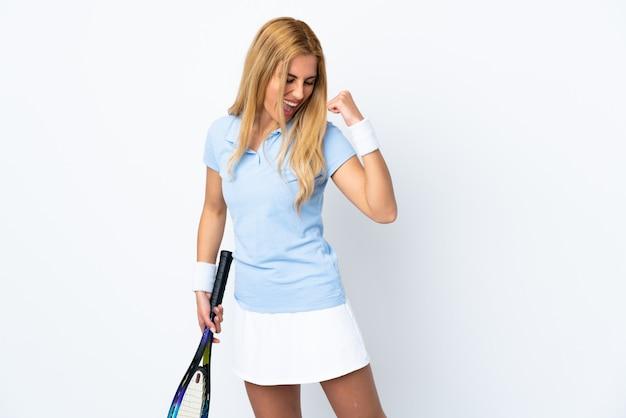 Jovem mulher loira uruguaia sobre parede branca jogando tênis e comemorando uma vitória