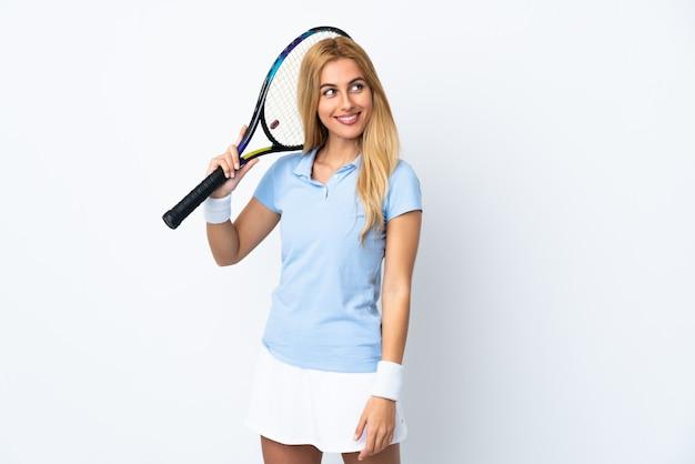 Jovem mulher loira uruguaia sobre parede branca jogando tênis e olhando para cima