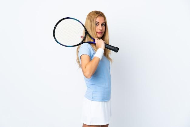 Jovem mulher loira uruguaia sobre parede branca jogando tênis