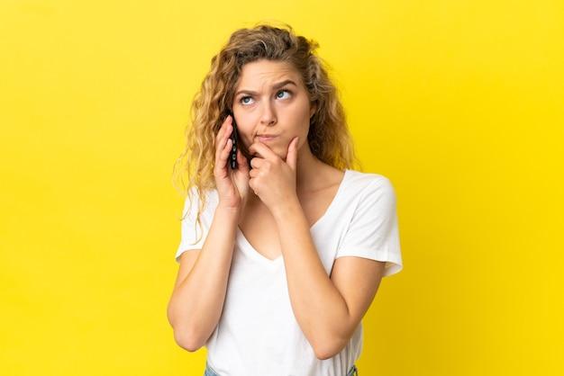 Jovem mulher loira usando celular isolado em um fundo amarelo, tendo dúvidas