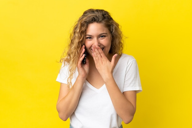 Jovem mulher loira usando telefone celular isolado em um fundo amarelo feliz e sorridente, cobrindo a boca com a mão