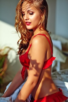 Jovem mulher loira, vestindo lingerie vermelha, sentado na cama de manhã