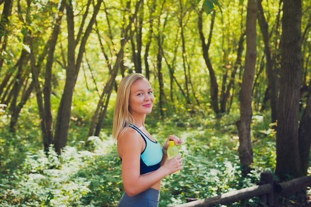 Jovem mulher loira vestindo top esporte e segurando a garrafa de água
