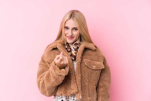 Jovem mulher loira, vestindo um casaco contra um fundo rosa, apontando com o dedo para você, como se convidando se aproximar.