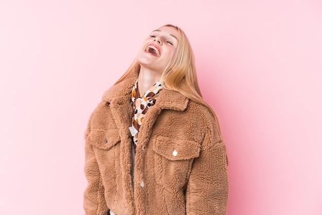 Jovem mulher loira, vestindo um casaco contra uma parede rosa relaxado e feliz rindo, pescoço esticado, mostrando os dentes.