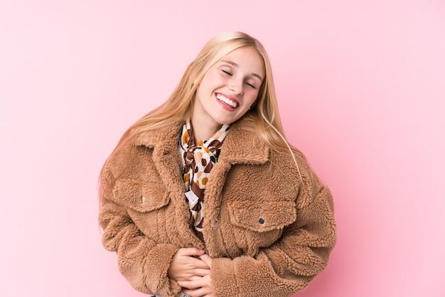 Jovem mulher loira, vestindo um casaco contra uma parede rosa ri alegremente e se diverte mantendo as mãos no estômago.