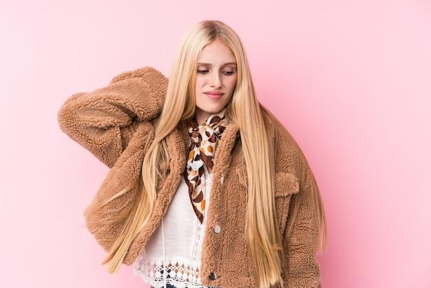 Jovem mulher loira, vestindo um casaco contra uma parede rosa, sofrendo dores no pescoço devido ao estilo de vida sedentário.