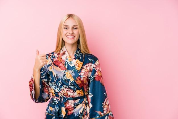 Jovem mulher loira, vestindo um pijama de quimono sorrindo e levantando o polegar