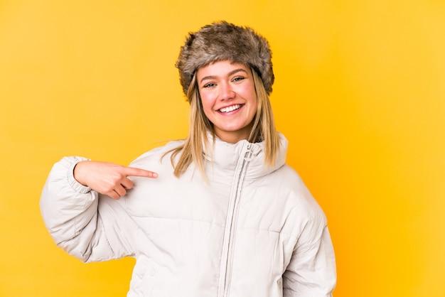 Jovem mulher loira vestindo uma roupa de inverno isolada jovem mulher loira isolada em amarelo