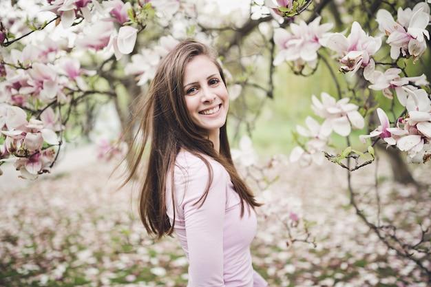 Jovem mulher longa alegre do cabelo sob a magnólia de florescência.