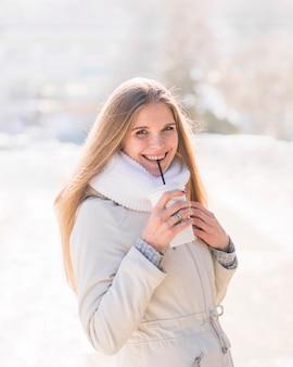 Jovem mulher loura de sorriso que bebe o copo de café descartável no inverno