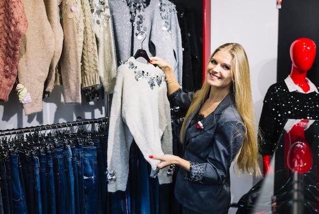 Jovem mulher loura de sorriso que escolhe a camisola cinzenta na loja