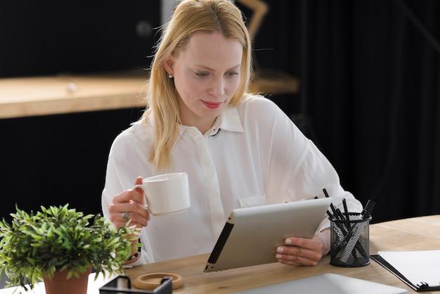 Jovem mulher loura de sorriso que guarda a xícara de café que olha a tabuleta digital