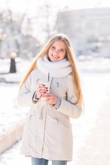 Jovem mulher loura de sorriso que guarda o copo de café descartável no inverno