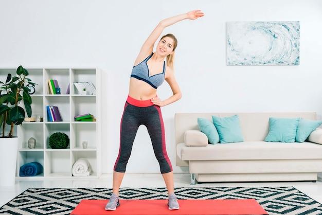 Jovem mulher loura feliz que faz esticando o exercício em casa