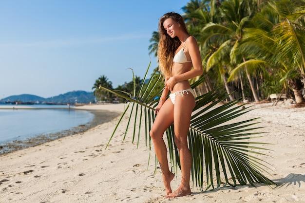 Jovem mulher magra em maiô de biquíni branco, segurando uma folha de palmeira tomando banho de sol na praia tropical.