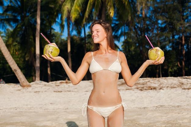 Jovem mulher magra em trajes de banho de biquíni branco segurando cocos, sorrindo, tomando banho de sol na praia tropical.