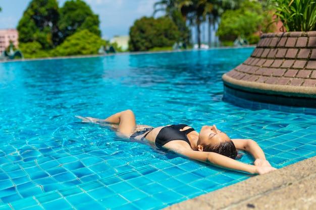 Jovem mulher magro sexy relaxante na piscina tropical com água azul cristalina em dia quente de verão