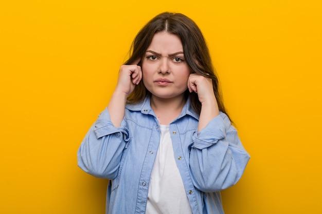 Jovem mulher mais curvilínea e mais focada em uma tarefa, mantendo os dedos indicadores apontando para a cabeça.