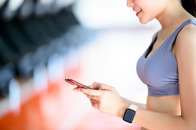 Jovem, mulher, malhação, em, ginásio, usando, telefone móvel, em, ginásio