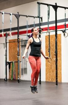 Jovem mulher malhando com uma corda de pular