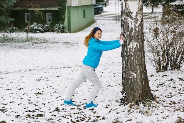 Jovem mulher malhando debaixo da árvore na paisagem de neve
