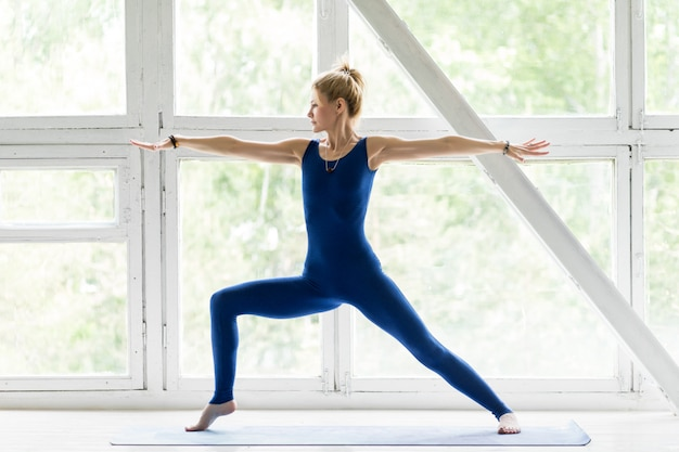 Jovem mulher malhando, fazendo exercícios de ioga ou pilates