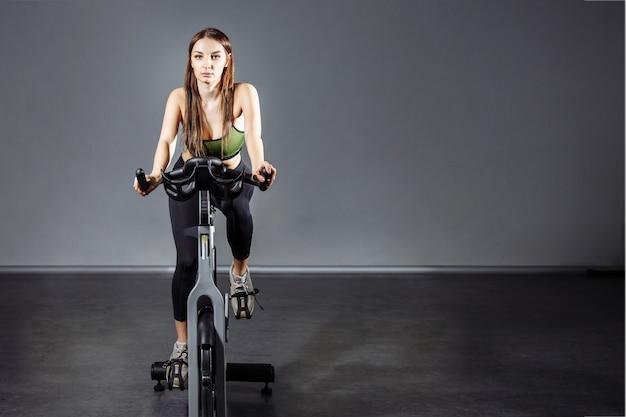 Jovem mulher malhando na bicicleta de exercício no ginásio.