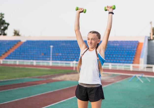 Jovem mulher mãos exercício com pesos