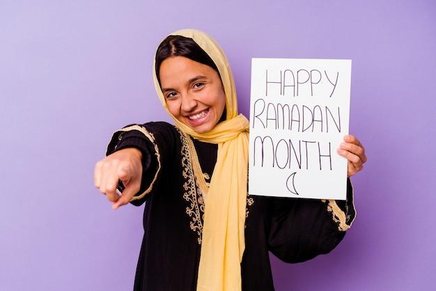 Jovem mulher marroquina segurando um cartaz feliz do ramadã isolado na parede roxa