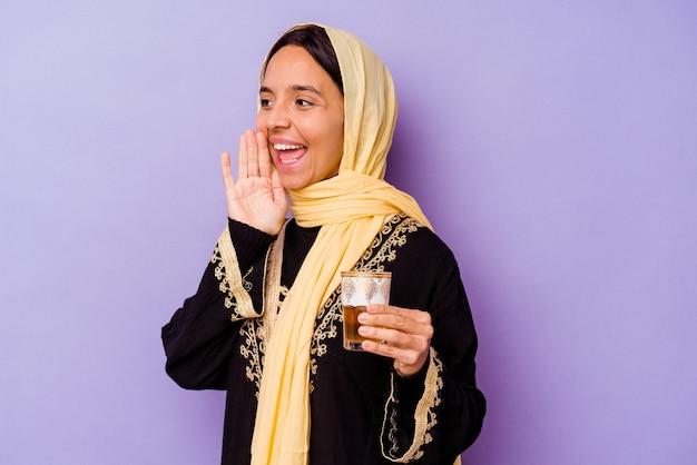 Jovem mulher marroquina segurando um copo de chá isolado no fundo roxo, gritando e segurando a palma da mão perto da boca aberta.