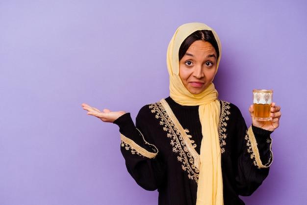 Jovem mulher marroquina segurando um copo de chá isolado no fundo roxo, mostrando um espaço de cópia na palma da mão e segurando a outra mão na cintura.