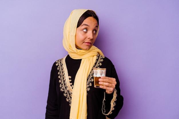 Jovem mulher marroquina segurando um copo de chá isolado no fundo roxo parece de lado sorrindo, alegre e agradável.