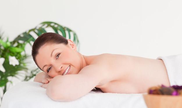 Jovem, mulher, massagem, tabela, sorrindo, câmera