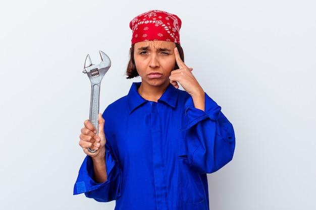 Jovem mulher mecânica segurando uma chave isolada apontando templo com o dedo, pensando, focada em uma tarefa.