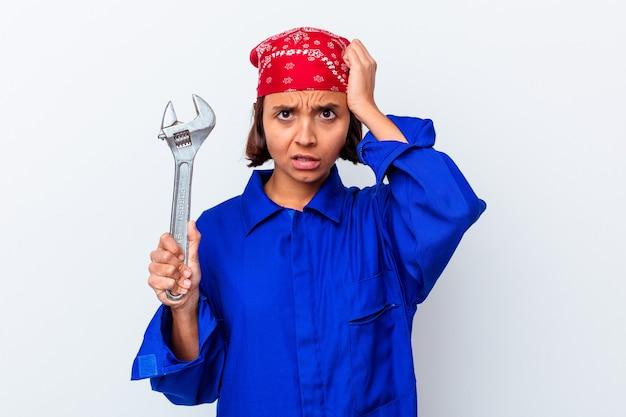 Jovem mulher mecânica segurando uma chave isolada em choque, ela se lembrou de uma reunião importante.