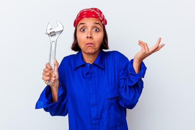 Jovem mulher mecânica segurando uma chave isolada encolhe os ombros e abre os olhos confusos.
