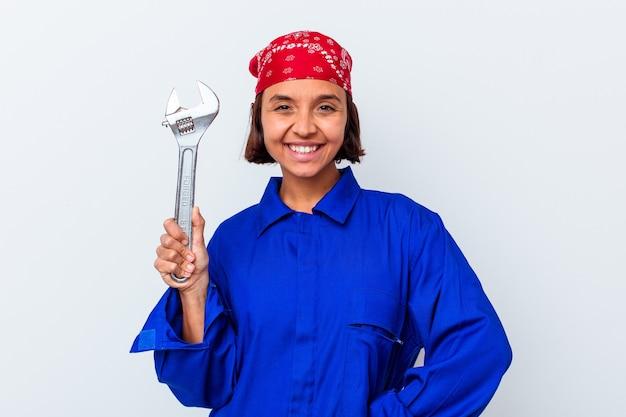 Jovem mulher mecânica segurando uma chave isolada feliz, sorridente e alegre.