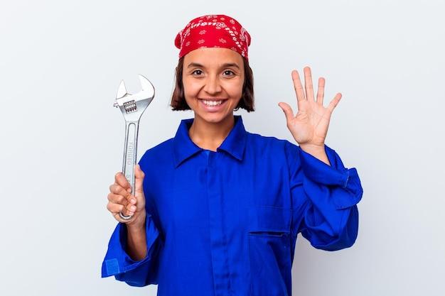 Jovem mulher mecânica segurando uma chave isolada sorrindo alegre mostrando o número cinco com os dedos.