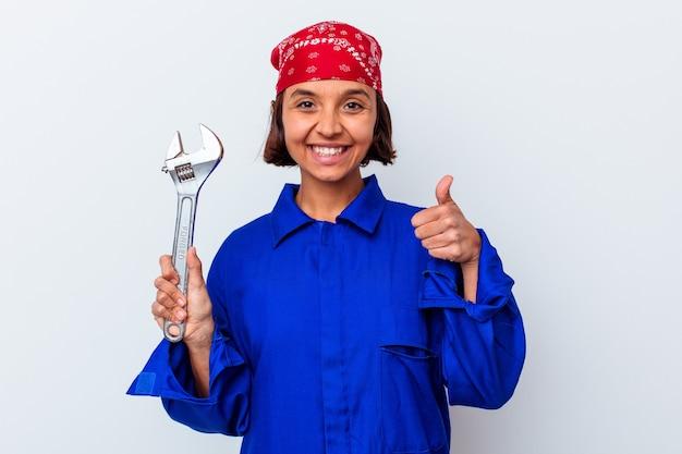 Jovem mulher mecânica segurando uma chave isolada, sorrindo e levantando o polegar
