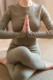 Jovem mulher meditando em casa de perto