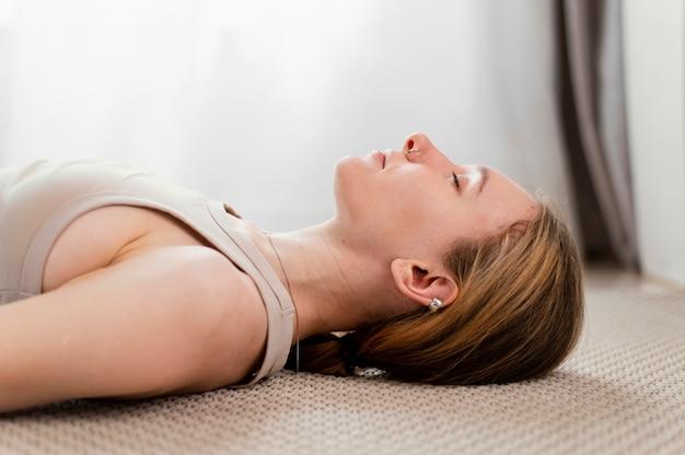 Jovem mulher meditando em casa deitada no chão