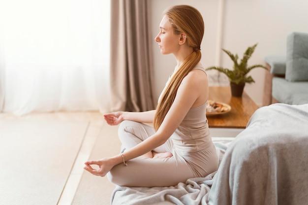 Jovem mulher meditando em casa, vista lateral