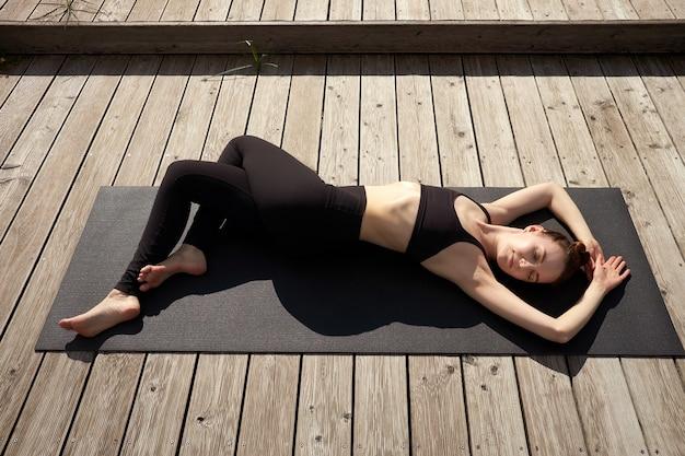 Jovem mulher meditando, relaxando e praticando ioga no cais de madeira perto do lago.