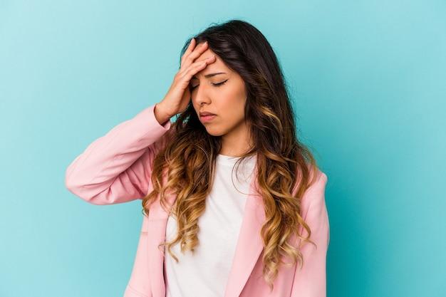 Jovem mulher mexicana isolada em um fundo azul, tocando as têmporas e tendo dor de cabeça.