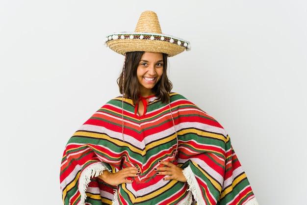 Jovem mulher mexicana isolada na parede branca confiante, mantendo as mãos nos quadris.