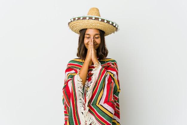 Jovem mulher mexicana isolada no fundo branco, de mãos dadas para rezar perto da boca, sente-se confiante.