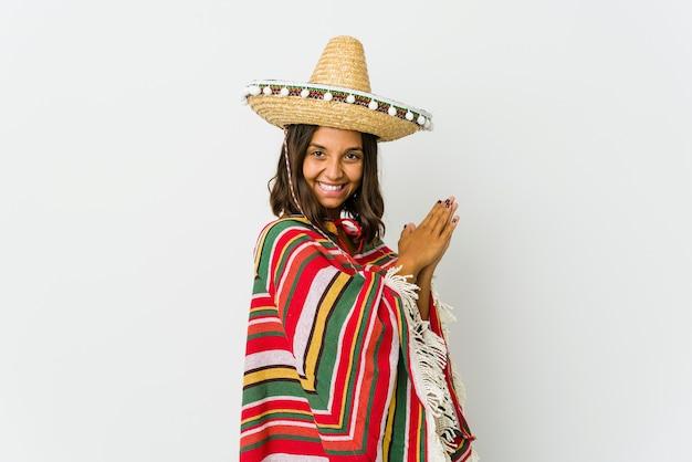 Jovem mulher mexicana isolada no fundo branco, sentindo-se enérgica e confortável, esfregando as mãos com confiança.